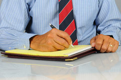 Businessman writing in note pad Royalty Free Stock Photos