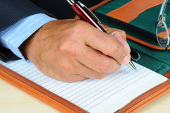 Businessman writing in note pad. Closeup of a businessman writing in notebook. Vertical format showing only hand, pen and notebook, with shallow depth of field Royalty Free Stock Image