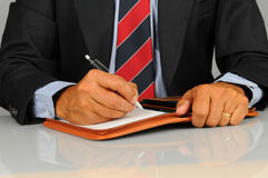 Businessman writing in note pad Royalty Free Stock Images