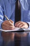 Businessman Writing in Notebook. A young businessman writes in a notebook while sitting at a desk Stock Photo