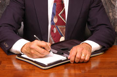 Businessman Writing in Notebook Stock Image