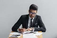 Businessman writing in a notebook on a grey background in a cafe, the tablet, telephone and papers on the table. Stock Photos