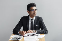 Businessman writing in a notebook and looks away from the camera, the tablet, telephone and papers on the table Stock Images