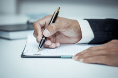 Businessman writing on notebook with pen in the office. In blue color tone Royalty Free Stock Photography