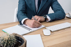 Businessman writing in notebook while sitting at office table Royalty Free Stock Photo