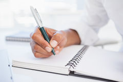 Businessman writing in notepad at desk Royalty Free Stock Image