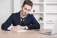 Businessman writing in notepad Stock Photo