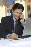 Businessman Writing Notes While On Call Stock Image