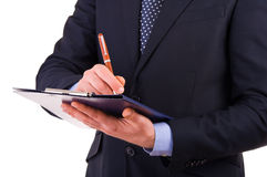 Businessman writing notes on clipboard. Stock Image