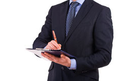 Businessman writing notes on clipboard. Stock Photography