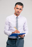 Businessman writing notes in clipboard Stock Photos