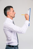 Businessman writing notes in clipboard Stock Images