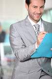 Businessman writing notes in a folder Stock Photo