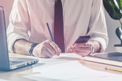 Businessman writing notes from mobile phone at office desk Stock Image