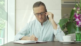Businessman writing notes in personal organizer while talking on mobile phone with client. stock footage