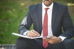 Businessman writing notes while sitting on a bench Stock Photo