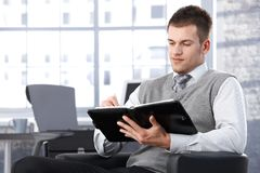Businessman writing notes to personal organizer. Young businessman sitting in bright office, writing notes to personal organizer Royalty Free Stock Photos