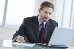 Businessman Writing Notes While Using Laptop At Desk Royalty Free Stock Images