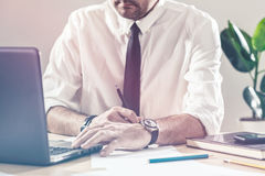 Businessman writing notes and using laptop at office desk Royalty Free Stock Images