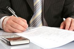 Businessman Writing On A Form Stock Image