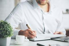 Businessman writing in organizer Stock Photo