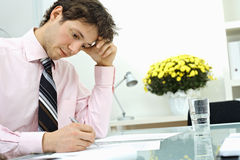 Businessman writing on paper Stock Image