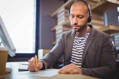 Businessman writing on paper while communicating with headphones Royalty Free Stock Images