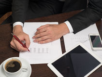 Businessman writing on the paper next to the tablet, coffee, cell phone Stock Images