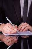 Businessman Writing On Paper With Pen Royalty Free Stock Images