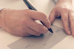 Businessman writing a payment check. Close up of a businessman writing a payment check Stock Image