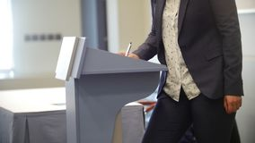 Businessman writing with a pen near the podium