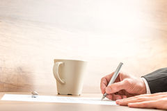 Businessman writing with a pen on a paper sheet. Hands of a businessman writing with a silver pen on a paper sheet, at a wooden desk, next to a mug of coffee or Royalty Free Stock Photography