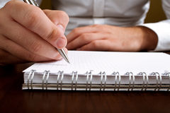 Businessman writing with pencil. Businessman writing a note with pencil Stock Photos