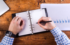 Businessman writing into personal organizer. Chart graph, wooden Stock Photography