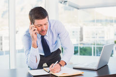 Businessman writing and phoning at his desk Royalty Free Stock Image