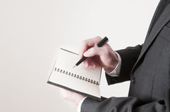 Businessman Writing in a Planner Stock Images