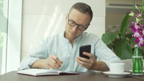 Businessman writing in daily planner and check notes on smartphone stock video