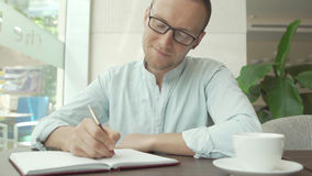 Businessman writing in the daily planner, diary. And wear glasses Royalty Free Stock Images