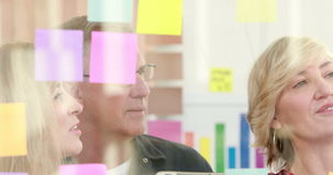 Businessman writing on post it with his colleagues stock video