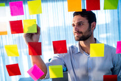 Businessman writing on post it Stock Photos