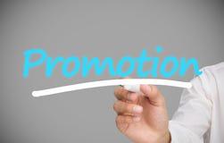 Businessman writing promotion. On grey background Stock Photo
