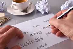 Businessman writing relevant business words on sheet business co. Businessman writing relevant business words on sheet on gray office table with crumpled sheets Royalty Free Stock Images