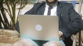 Businessman is writing a report on his laptop in tropical beach. The man in black jacket and tie is sitting on comfortable deck-chair and preraring for stock video