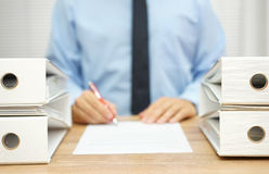 Businessman is writing report about irregularities in company Royalty Free Stock Image