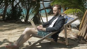 Businessman is writing report on the tropical beach. Young man with beard is sitting on comfortable deck-chair near the palms and holding his brand-new device stock video