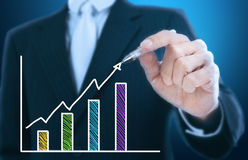 Businessman writing rising graph Stock Images