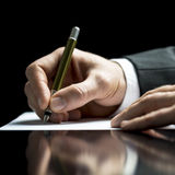 Businessman writing on a sheet of white paper. With a fountain pen as he signs an agreement or contract, writes correspondence, takes notes or completes a Stock Photography