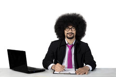 Businessman writing and smiling at the camera Royalty Free Stock Photography