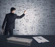 Businessman writing strategy plan on wall Stock Photo