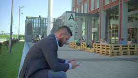 Businessman writing text message on smartphone. He is sitting on the wall during break of the work. He is young and has beard. Man is dressed in suit and shirt stock footage